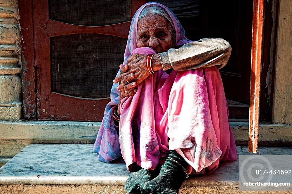 Portrait of an elderly woman wearing a pink sari and sitting at a doorway Jodhpur, Rajasthan, India