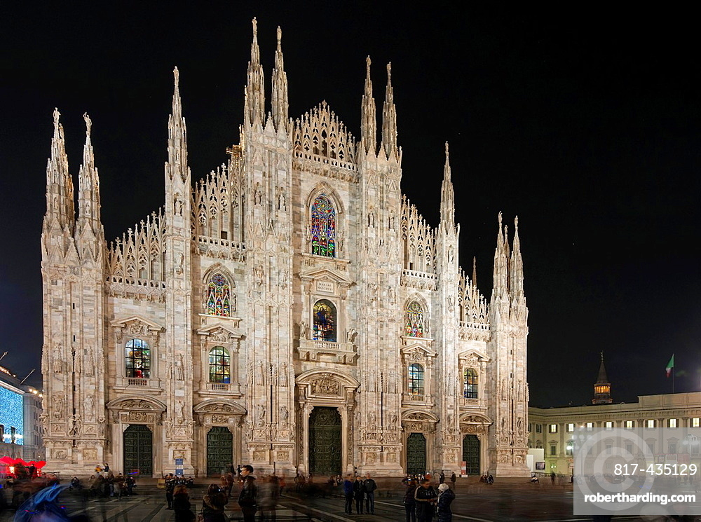 illuminated facade and decorated glass windows of cathedral at night, in foreground shadows of people in the square