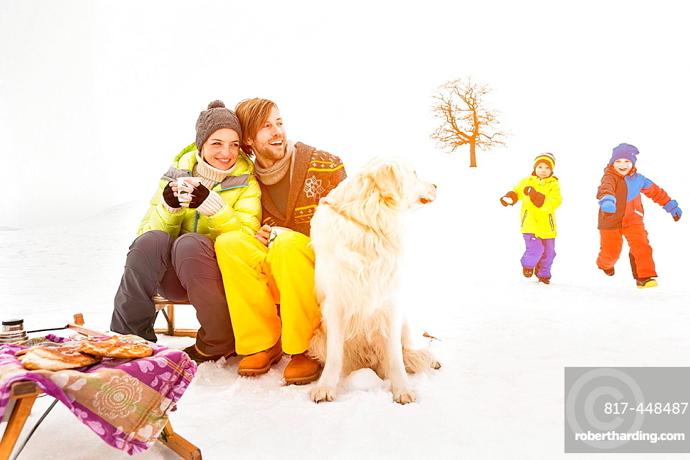 Parents with dog and children playing in background