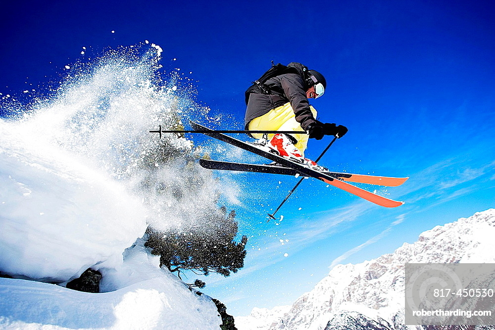 Male skier mid air on mountain