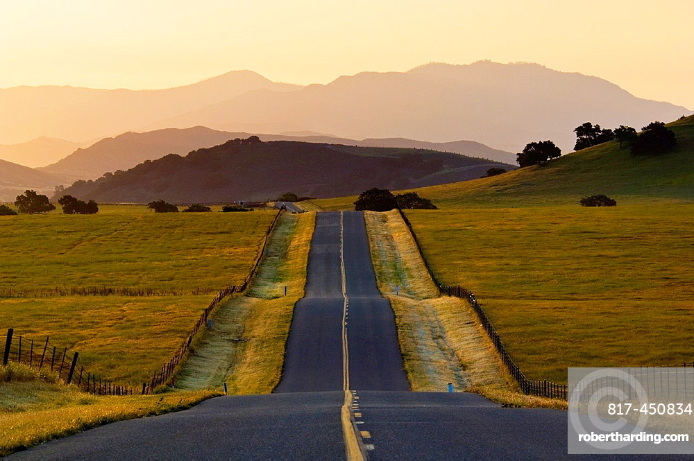 Golden sunrise light over long straight two lane country road and rolling hills in Spring, Santa Ynez Valley, California.