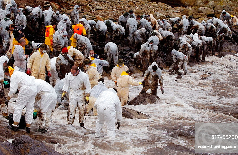 Volunteers dressed with protective clothing gathering the fuel spill ('chapapote') of Prestige tanker, Dec, 2002, Galicia, Spain