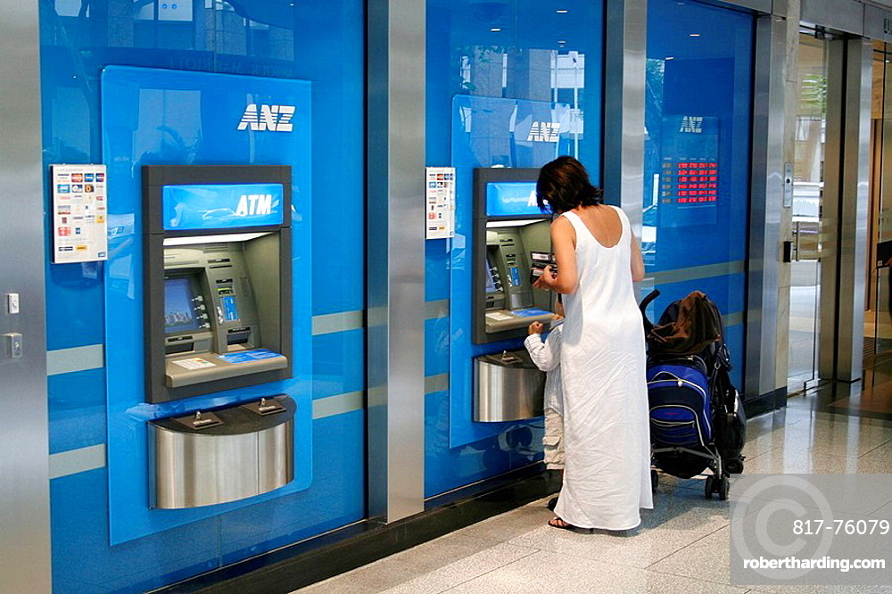 Mother with kid on ATM machine in national bank, George St., Sydney, New South Wales, Australia