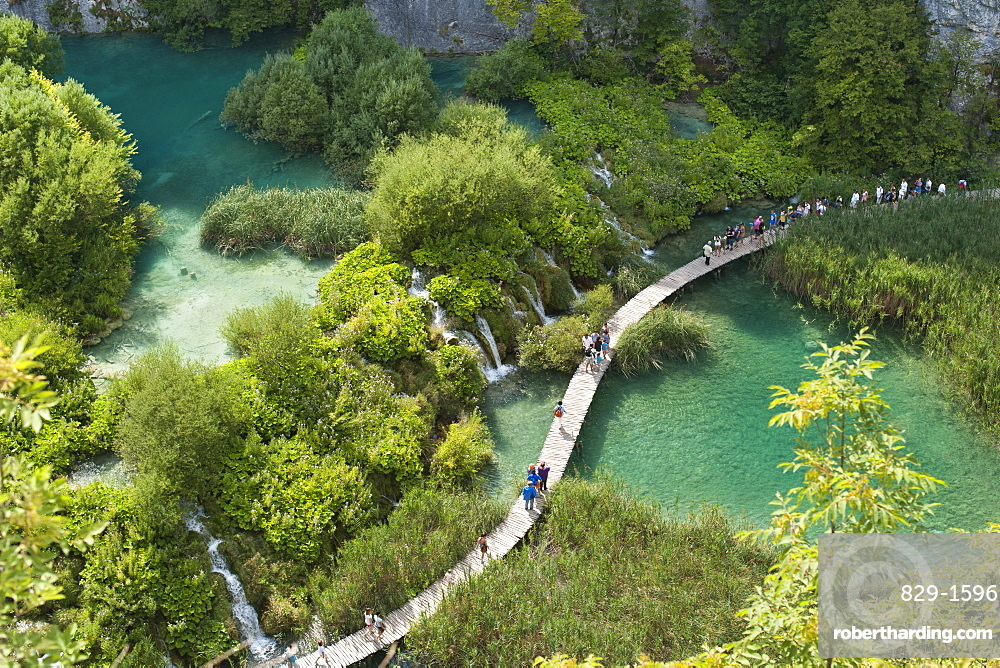 Tourists walking along wooden walkways in Plitvice Lakes National Park, UNESCO World Heritage Site, Croatia, Europe
