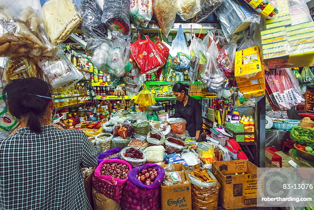Woman and well-stocked stall selling goods and groceries at this huge old market, Central Market, city centre, Phnom Penh, Cambodia, Indochina, Southeast Asia, Asia