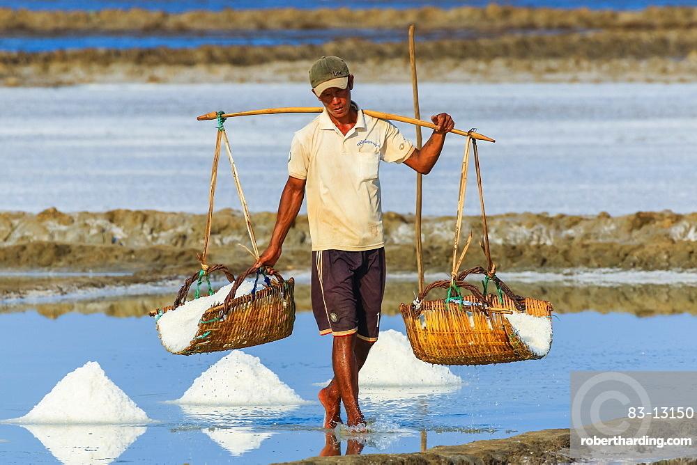 Man with shoulder pole harvesting the salt fields around the Praek Tuek Chhu River estuary south of the city, Kampot, Cambodia, Indochina, Southeast Asia, Asia