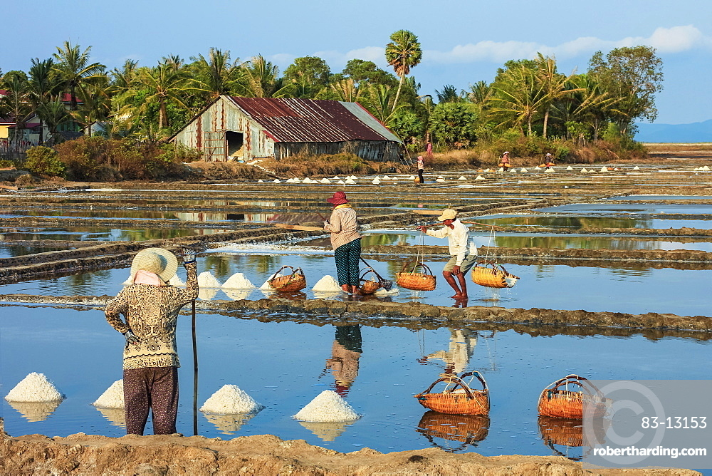Piles of salt and workers harvesting the salt fields around the Praek Tuek Chhu River estuary south of the city, Kampot, Cambodia, Indochina, Southeast Asia, Asia