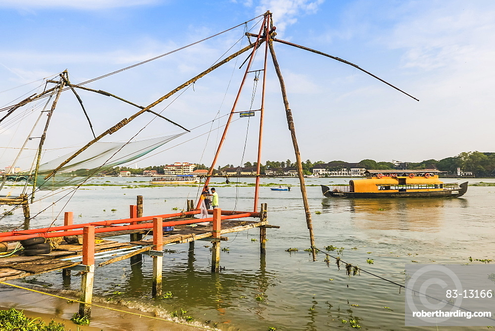 Old Chinese fishing nets & tour boat on the waterfront of Vypin Island with Fort Cochin beyond; Fort Vypin, Kochi, Kerala, India