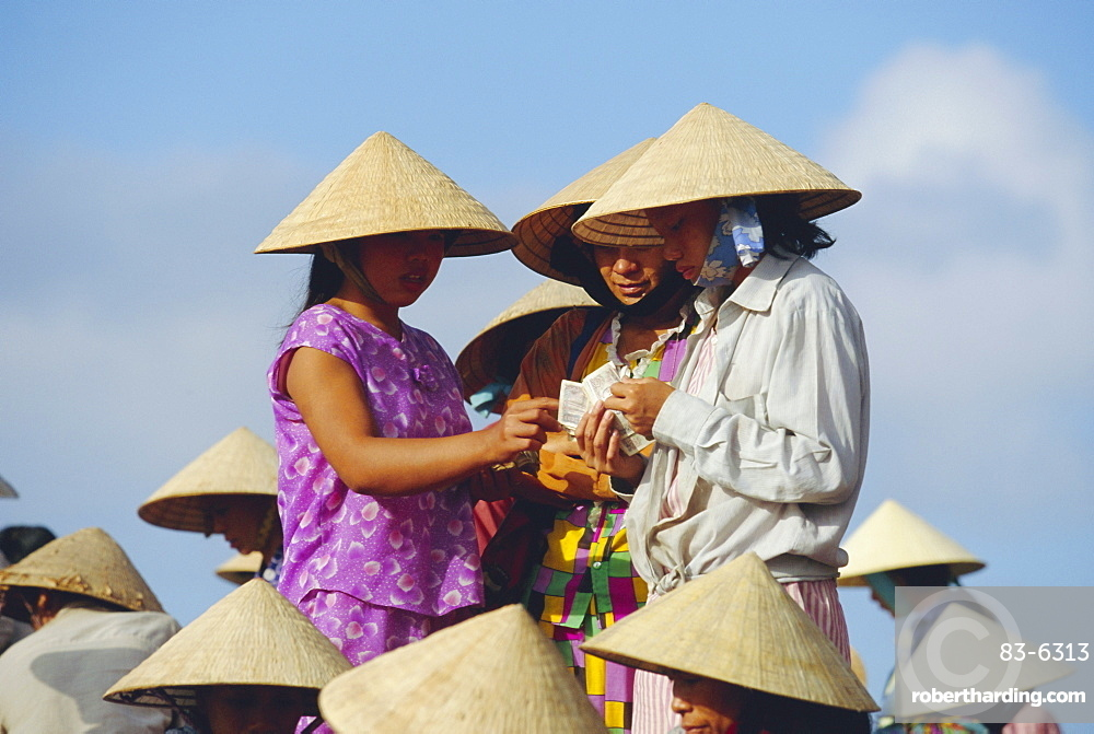 Women in conical hats counting money at the fish market by the Thu Bon River in Hoi An, south of Danang, Vietnam, Indochina, Asia