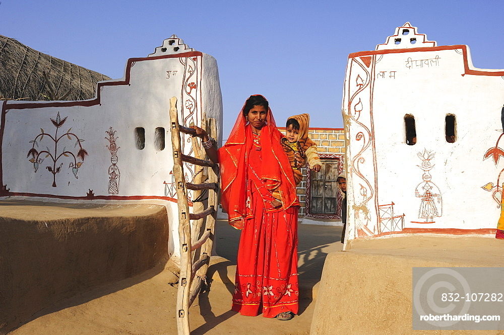 Woman in a sari with a toddler, traditionally painted entrance to a courtyard, Thar Desert, Rajasthan, North India, India, Asia