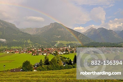 View across Oberstdorf with rainbow, Schattenberg mountain with Schattenberg ski jump at back, Oberallgaeu district, Bavaria, Germany, Europe