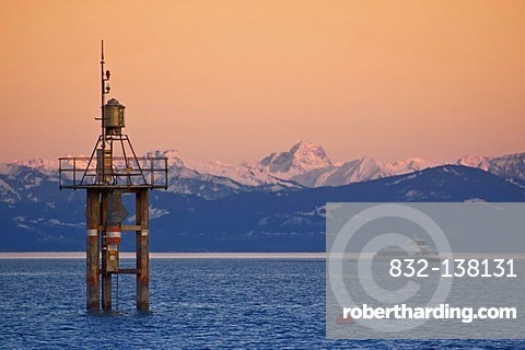 Lighthouse in Lake Constance with view to the mountain chain of the Alps in evening sky, Konstanz, Baden-Wuerttemberg, Germany, Europe