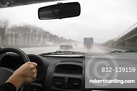 View through the windshield of a moving car at poor sight caused by heavy rain, Germany