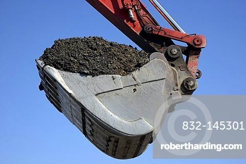 Excavator shovel, laden with soil, construction site