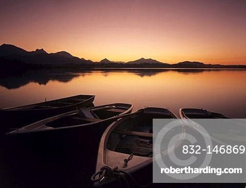 Rowing boats on Hopfensee lake after sunset, Ostallgaeu district, Bavaria, Germany, Europe
