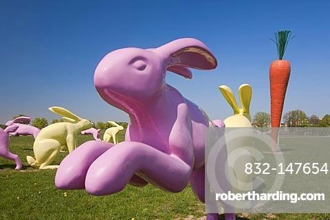 Bunny sculptures arranged around a carrot sculpture, Scharnhauser Park district, Ostfildern, Baden-Wuerttemberg, Germany, Europe