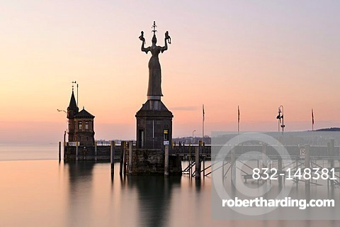 The harbor pier at the entrance of Constance harbor just before sunrise, the tide gauge with the Imperia Statue on it, the town's landmark, and the Molenhaeuschen building at the back, district of Konstanz, Baden-Wuerttemberg, Germany, Europe
