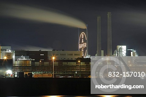 Bayer factory buildings and premises with the Rhine river in the foreground, night shot, Leverkusen, North Rhine-Westphalia, Germany, Europe