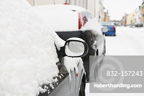 Right side mirror of a snow-covered black car and snow-covered road, winter, Germany