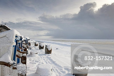 Snow-covered wicker beach chairs overlooking a snow and ice landscape on the south beach of Wyk of the North Sea island of Foehr, Nationalpark Schleswig-Holsteinisches Wattenmeer, Schleswig-Holstein Wadden Sea National Park, Unesco World Heritage Site, No