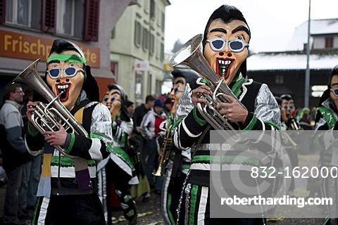 Guggenmusig Schaedubrommer group dressed to the theme of their 30 years anniversary during the carnival procession in Malters, Lucerne, Switzerland, Europe