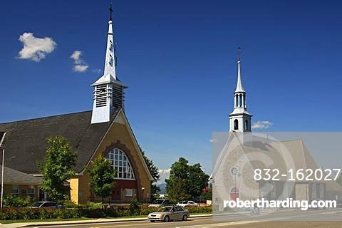 New church, left, and Saint-Pierre-et-Saint-Paul Church, historic monument in the town of St-Pierre-de-l'Ile-d'Orleans on Orleans Island, Quebec, Canada