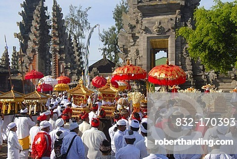 Balinese Hinduism, gathering of believers, ceremony, believers in bright temple dress carrying red parasols and shrines, temple tower and in the back the split gate, Candi bentar, Pura Ulun Danu Batur temple, Batur village, Bali, Indonesia, Southeast Asia