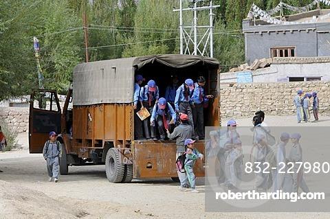 Schoolchildren in school uniform getting out of a truck that serves as a school bus, Secondary Senior School, Lamdon, Leh, Jammu and Kashmir, India, Himalayas, Asia