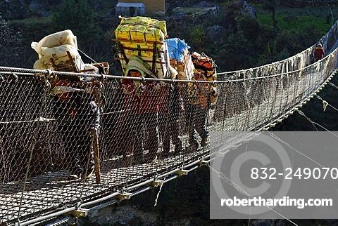 Carriers on Hillary Bridge over Dudh Koshi River, Khumbu Himal, Sagarmatha National Park, Nepal, Asia