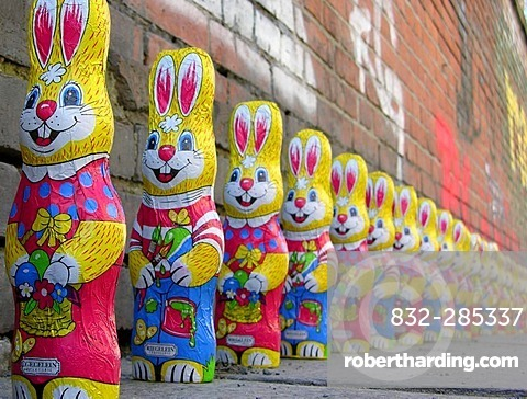 A group of over twenty easter bunnies from chocolate in a row in front of a wall with graffiti