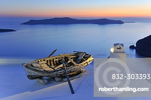 Old rowboat displayed on a rooftop terrace at sunset in front of the blue sea and the volcanic island of Nea Kameni, Thira, Fira, Santorini, Cyclades, Greece, Europe