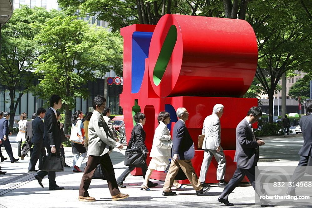 People on their way to work walking by Love-sculpture by American artist Robert Indiana, Shinjuku district, Tokyo, Japan, Asia