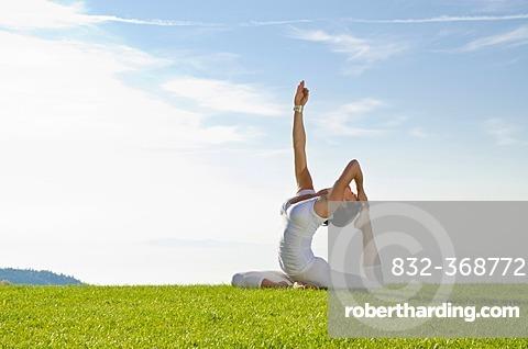 Young woman practising Hatha yoga outdoors, showing the pose kapotasana, dove pose, pigeon pose, Nove Mesto, Okres Teplice, Czech Republic, Europe