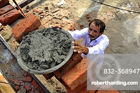 Man lifting pan with cement onto a scaffold, construction of brick houses for families whose houses were destroyed during the flood catastrophe of 2010, Lashari Wala village near Muzaffaragarh, Punjab, Pakistan, Asia