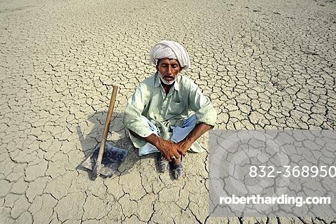 Farmer with closed eyes sitting on dried loamy soil, dreaming, Basti Lehar Walla village, Punjab, Pakistan, Asia