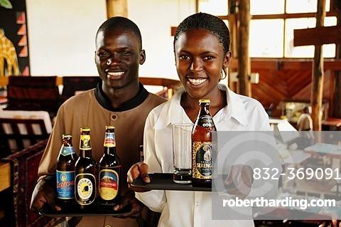 Waiter and waitress carrying the most popular beer brands in Tanzania, Serengeti, Kilimanjaro, Safari and Tusker, Lobo Wildlife Lodge, Serengeti National Park, Tanzania, Africa