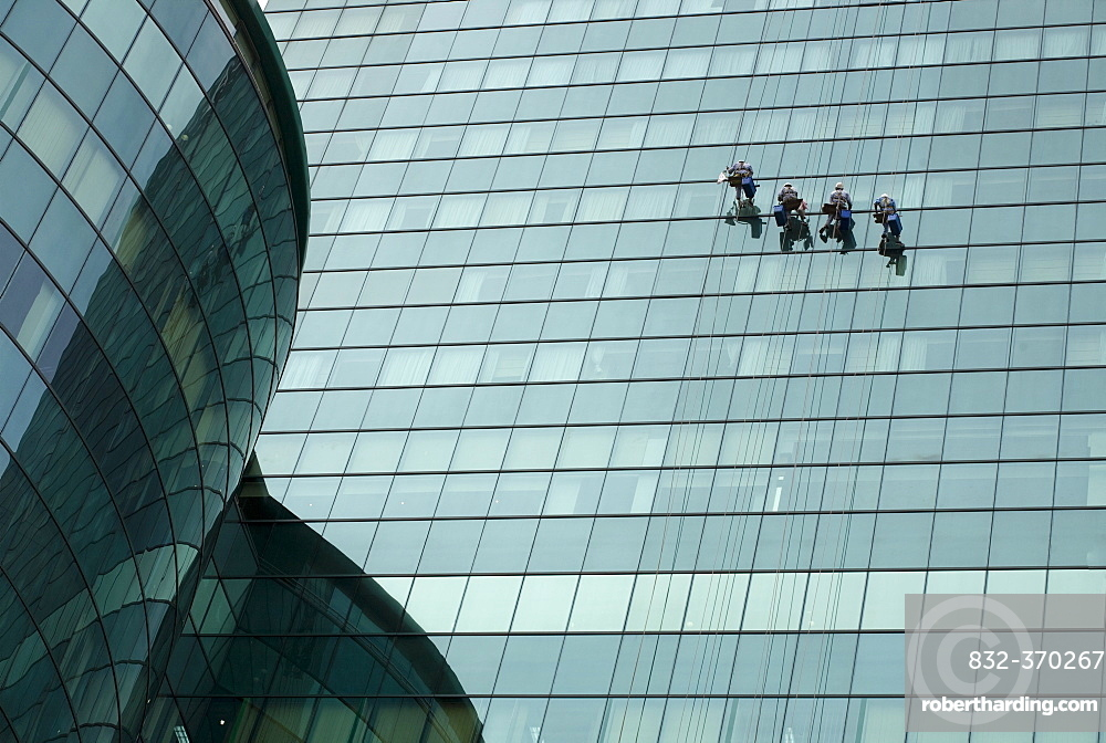 Window cleaners on a modern glass facade in Saigon, Ho Chi Minh City, Vietnam, Southeast Asia