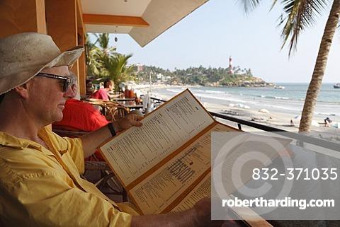 Tourist reading the menu of a cafe on Lighthouse Beach, Kovalam, Malabarian Coast, Malabar, Kerala state, India, Asia