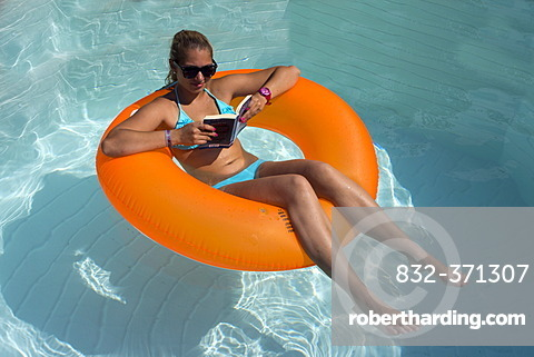 Young woman sitting on an inner tube, floating tyre, reading a paperback in a private swimming pool, Germany