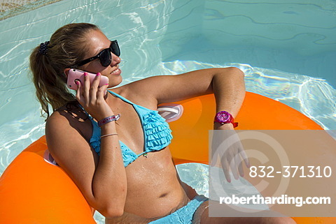 Young woman on an inner tube, floating tyre, talking on a mobile phone in a private swimming pool, Germany