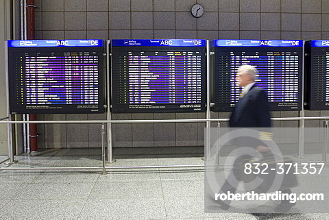 Pilot in front of flight info display screens, Terminal 2, Frankfurt Airport, Frankfurt, Hesse, Germany, Europe
