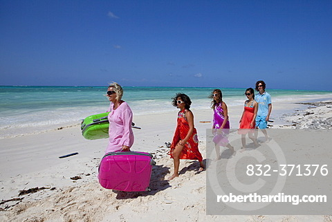 Mother on holiday carrying the suitcases for her family on her own on the beach