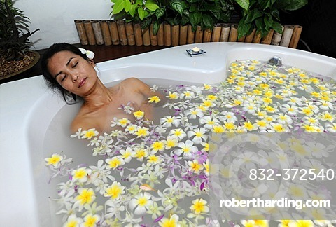 Woman in a sea of flowers in the tub, spa