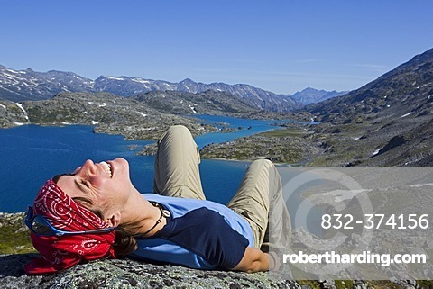 Young woman laughing, lying on a rock, relaxing, hiker enjoying the panorama on summit of historic Chilkoot Pass, Chilkoot Trail, Crater Lake behind, alpine tundra, Yukon Territory, British Columbia, B. C., Canada