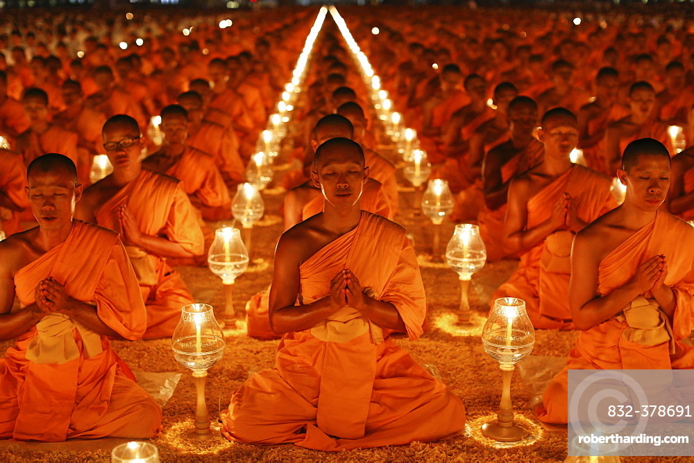 Monks sitting in rows praying and meditating by candlelight, Wat Phra Dhammakaya Temple, Khlong Luang District, Pathum Thani, Bangkok, Thailand, Asia
