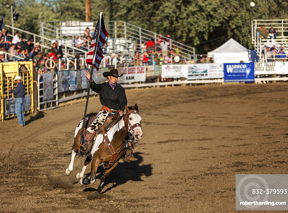 Cowgirl riding a horse, holding the flag of the United States, Fort Dalles, Oregon, USA, North America
