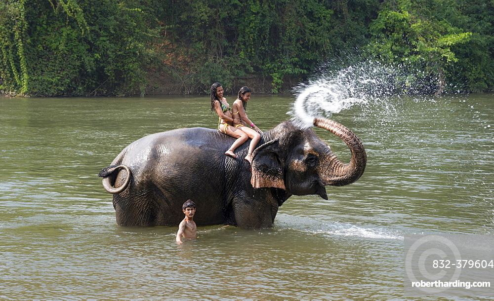 Elephant spraying two tourists, Kanchanaburi Province, Central Thailand, Thailand, Asia