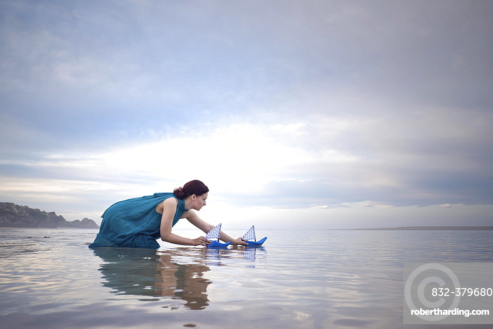 Woman with blue paper ships at low tide on the beach