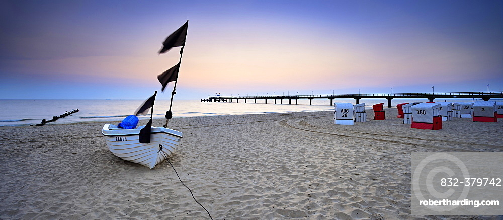 Fishing boat, pier and chairs on beach at sunrise, Baltic resort Bansin, Usedom, Mecklenburg-Western Pomerania, Germany, Europe