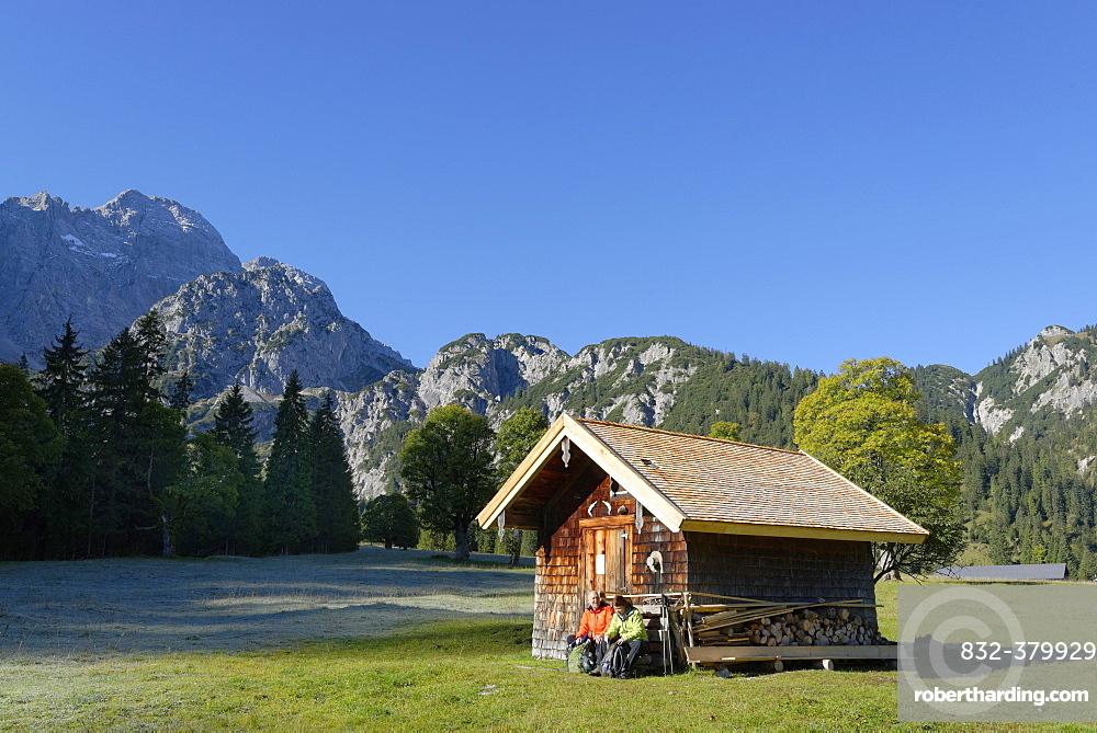 Hikers resting wooden hut, snacking, Rohntal at Purschalm, Eng, Karwendel, Risstal, Rissbachtal, Tyrol, Austria, Europe